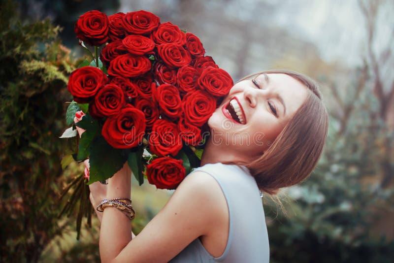 有一大花束的美丽的年轻女人 免版税库存图片