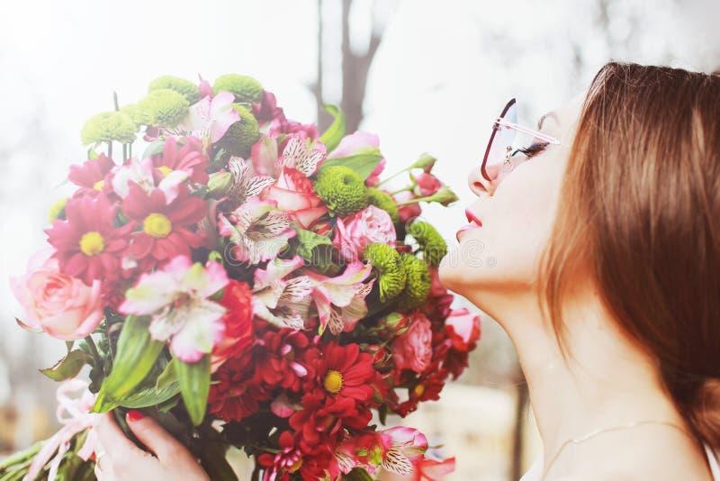 有一大花束的美丽的年轻女人 免版税图库摄影