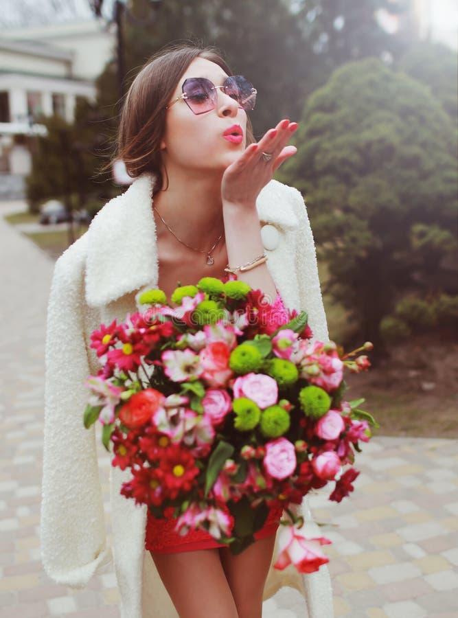 有一大花束的美丽的年轻女人 库存照片