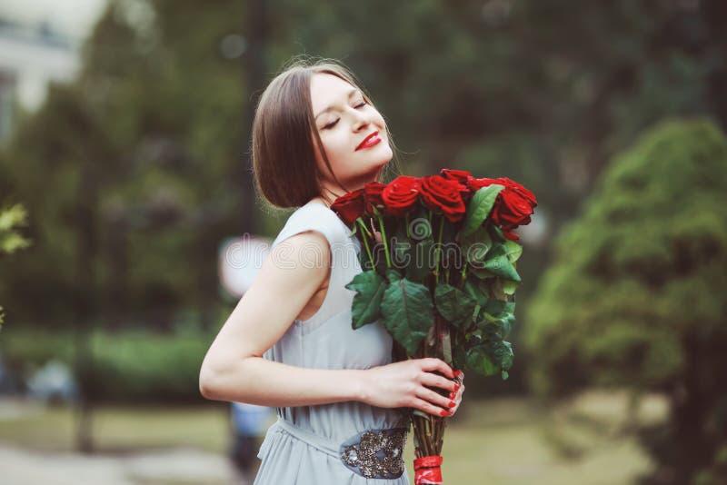 有一大花束的美丽的年轻女人 免版税库存照片