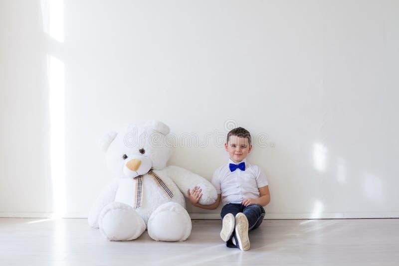 有一头大熊的一个软的玩具的男孩 免版税库存图片
