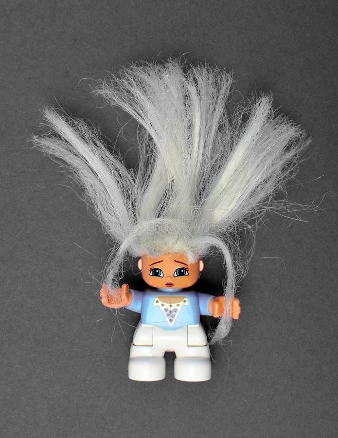 有一头干燥损坏的金发的逗人喜爱的玩具女孩,握她的头发  免版税库存照片