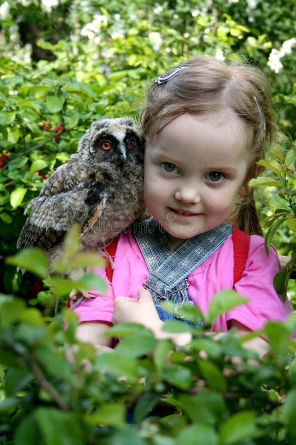 有一头猫头鹰的美丽的小女孩在她的肩膀 免版税图库摄影