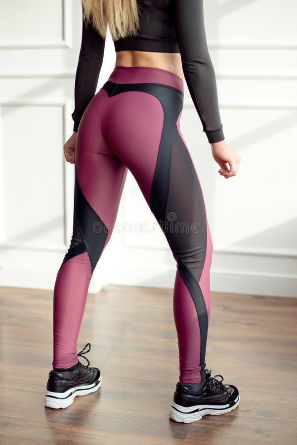 有一头运动身体站立在有大的明亮的瑜伽室的金发佩带在黑体育上面的和绑腿的年轻亭亭玉立的妇女 库存照片