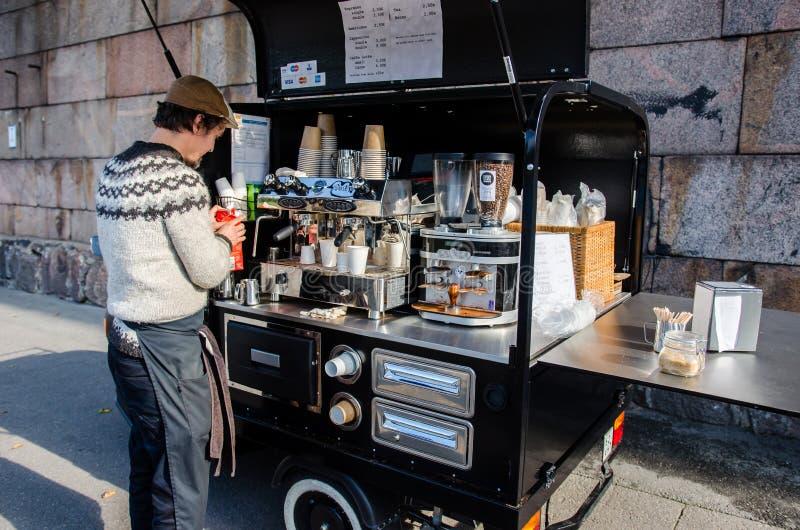 有一家微小的咖啡店的人在赫尔辛基,芬兰街道上  免版税库存图片