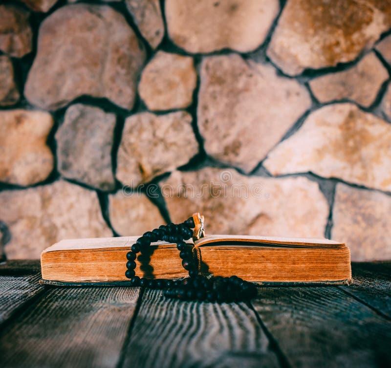 有一幅耶稣受难象的念珠在老木桌上的一本开放旧书在石墙背景  免版税库存图片