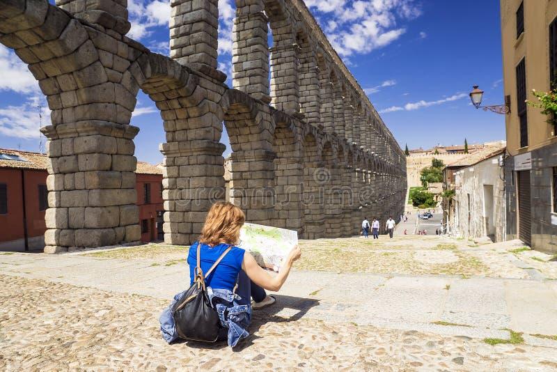 有一张地图的女孩在罗马渡槽的背景在Segov 库存照片