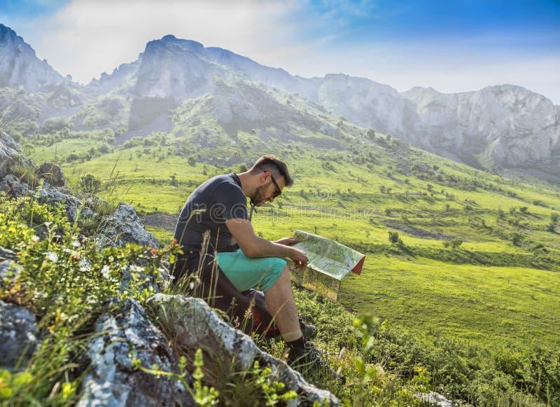 有一张地图的远足者在迷雾山脉 免版税图库摄影