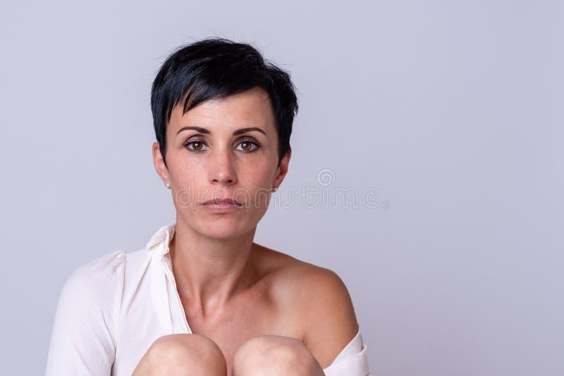 有一张小精灵似的面孔的可爱的成熟妇女 免版税库存图片