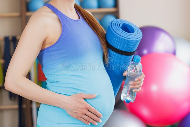 有一张席子的怀孕的运动的妇女瑜伽的在手上 免版税库存图片