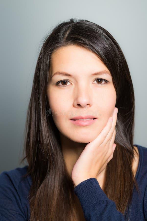 有一张平静的面孔的体贴的可爱的妇女 免版税库存照片