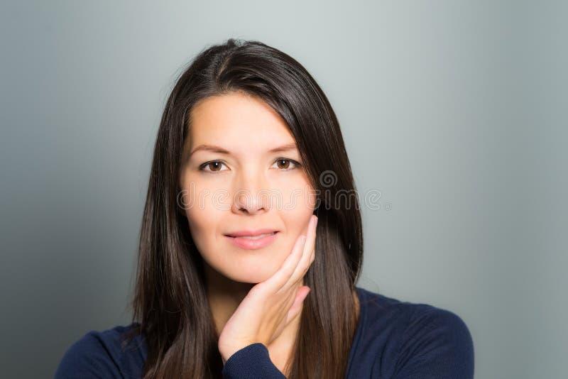 有一张平静的面孔的体贴的可爱的妇女 库存照片