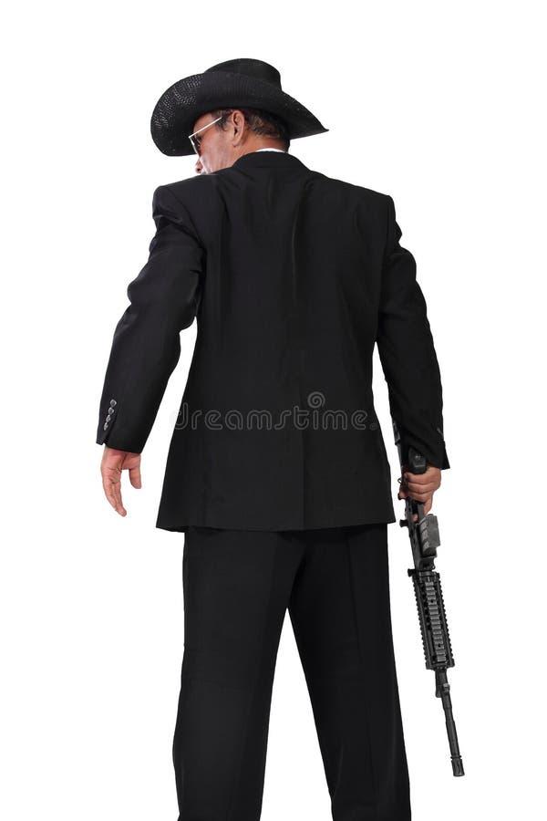 有一张枪后面射击的照片的职业杀手在白色 库存图片