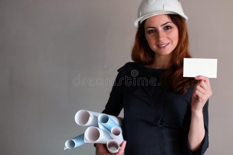 有一张空白的纸片的妇女在他的手上在建筑si 免版税库存图片
