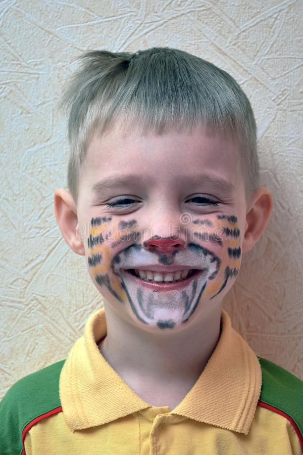 有一张被绘的面孔的一个小男孩以老虎的形式 微笑 免版税库存照片