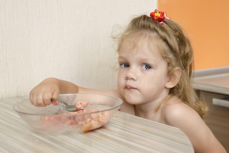 有一张阴沉的面孔的一个孩子吃粥 免版税库存图片