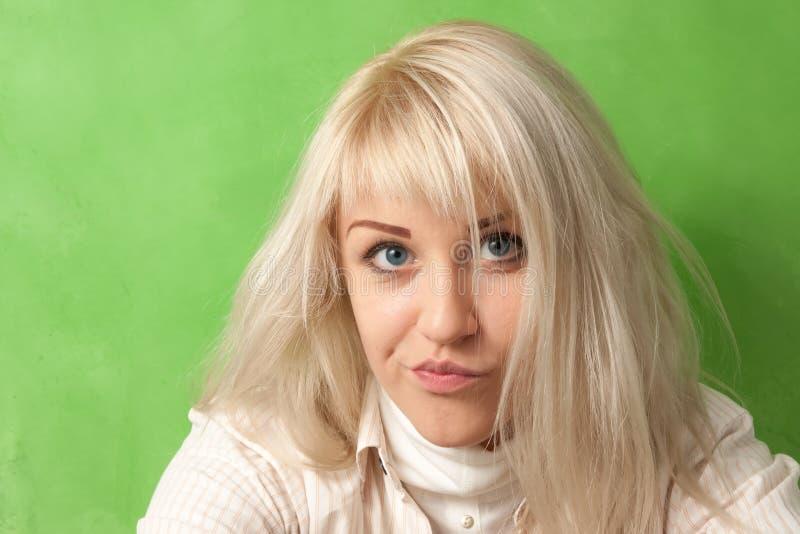 有一张滑稽的面孔的一个可爱的女孩 免版税库存照片
