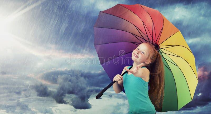 有一把五颜六色的伞的快乐的女孩 免版税库存图片