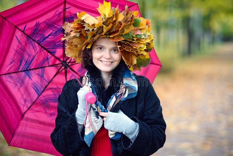 有一把伞的妇女在秋天公园 免版税库存图片