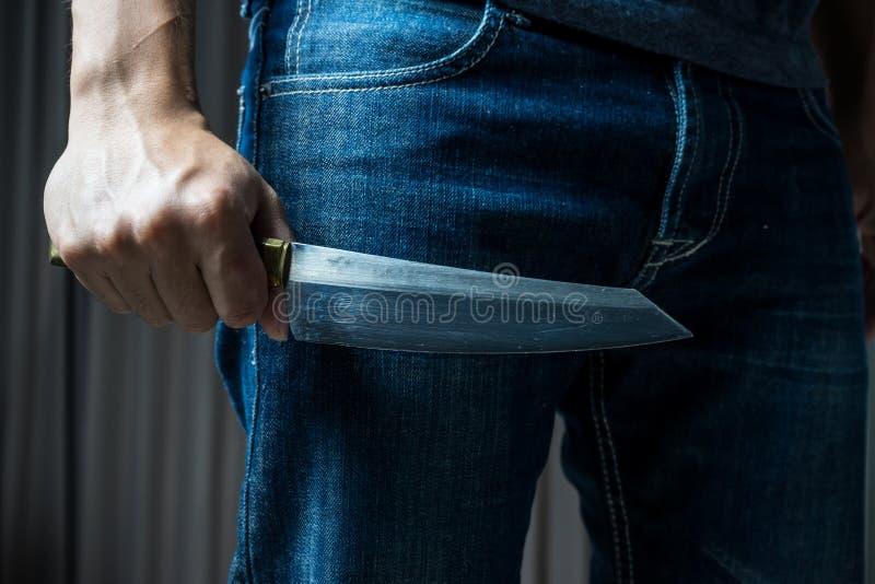 有一把刀子的人在一只手上,在黑暗的口气 库存图片