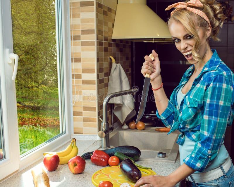 有一把刀子的年轻恼怒的呼喊的白肤金发的主妇在去的厨房里削减菜和厨师晚餐 图库摄影