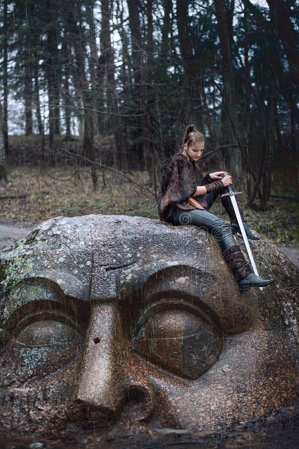有一把剑的女孩在一个石头 免版税库存照片