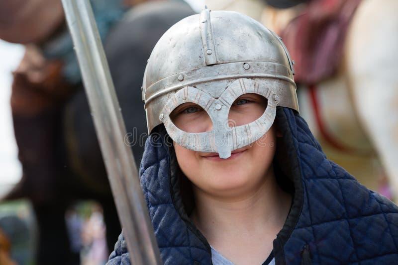 有一把剑的男孩在衣服俄国人战士 免版税库存照片