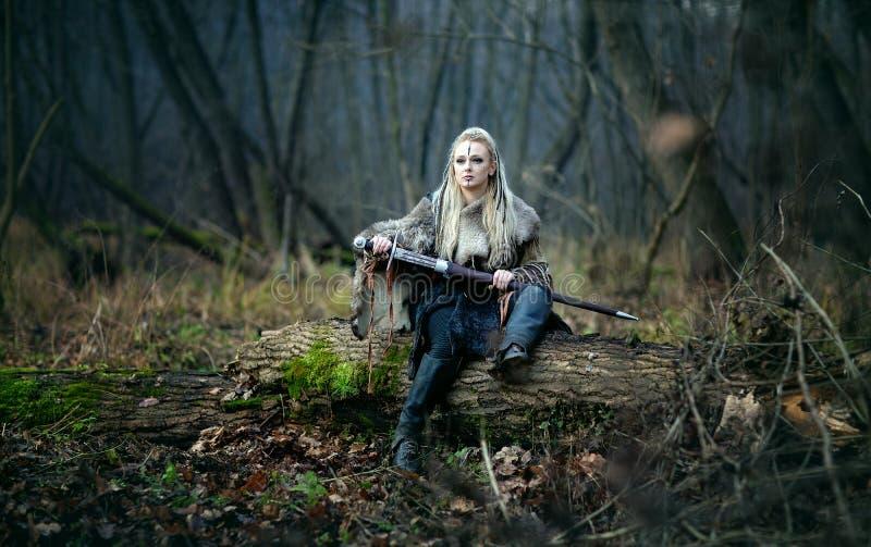 有一把剑的疯狂的愤怒的北欧海盗妇女战士在她的手上,在森林 库存照片