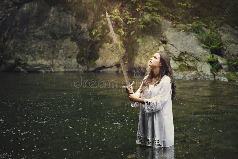 有一把剑的美丽的妇女在小河 库存照片
