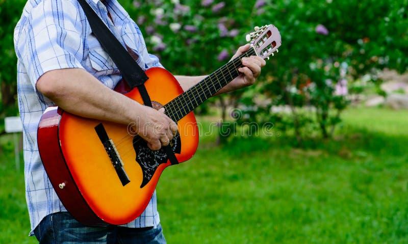 有一把吉他的人在他的手上 库存照片
