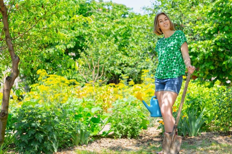 有一把喷壶的一年轻女人和一把铁锹在她的手上,参与从事园艺在她的庭院里 从事园艺的概念和 免版税库存照片