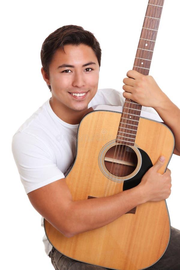 有一把声学吉他的可爱的人 库存照片