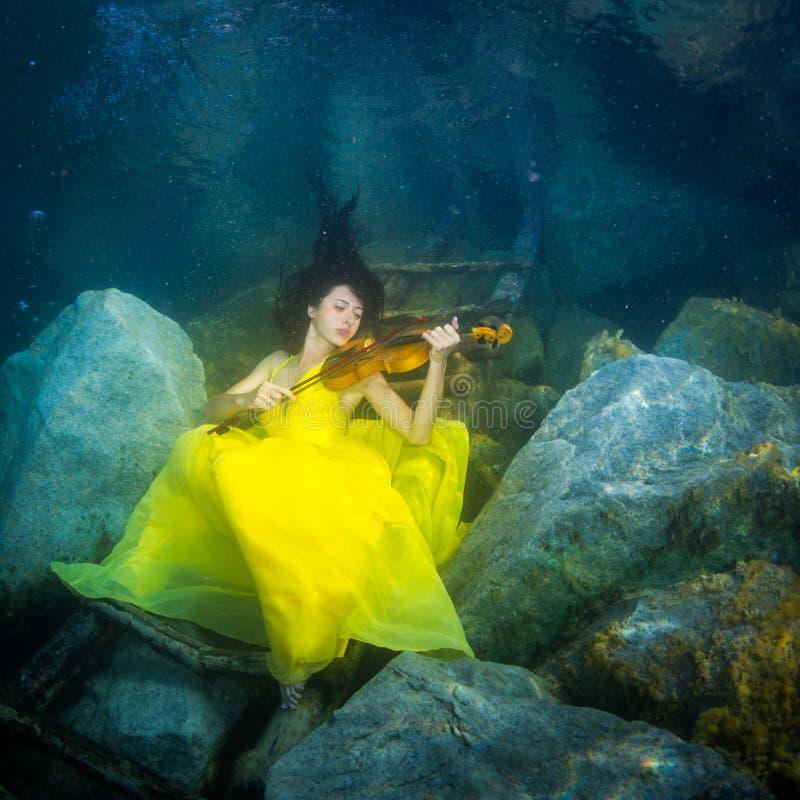 有一把小提琴的女孩在水下 免版税图库摄影