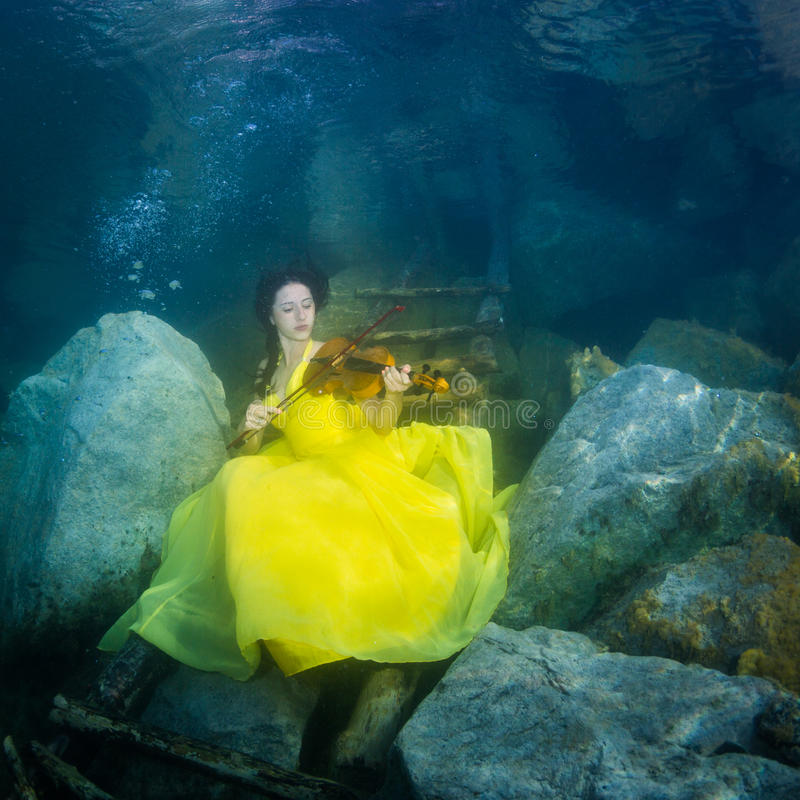 有一把小提琴的女孩在水下 库存照片