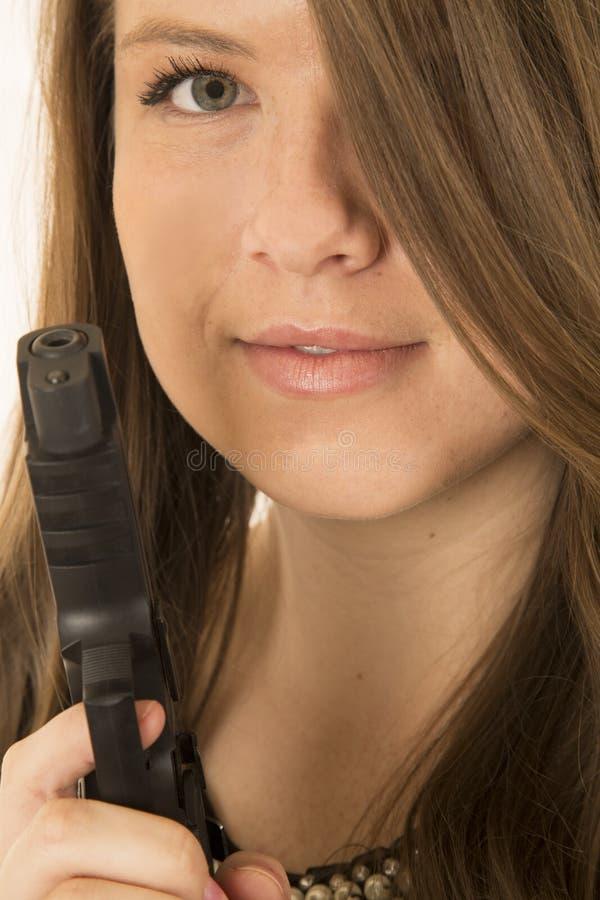 有一把手枪和她的头发的年轻深色的妇女一只眼睛 免版税图库摄影