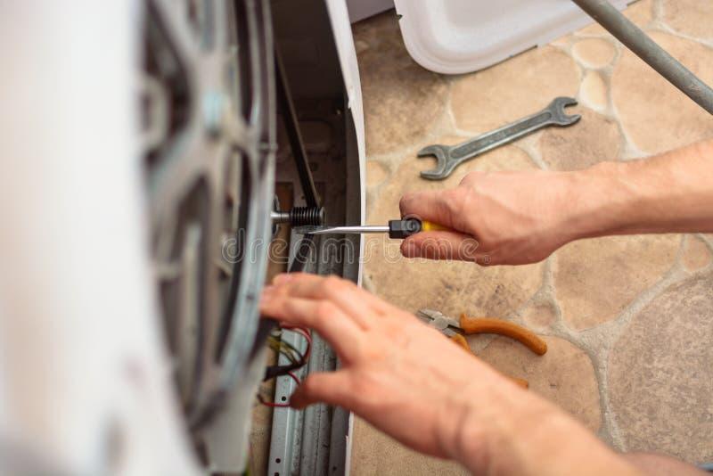 有一把扳手的人的手修理的洗衣机 库存图片