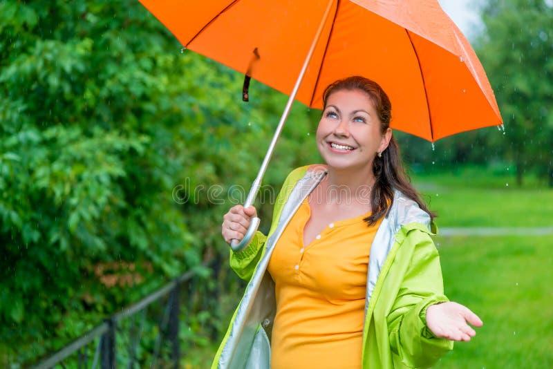 有一把明亮的橙色伞的女孩 免版税库存图片
