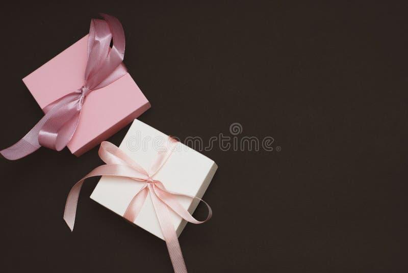 有一把桃红色和白色丝带弓的白色和桃红色礼物盒在布朗背景 平的位置,顶视图,拷贝空间 库存照片