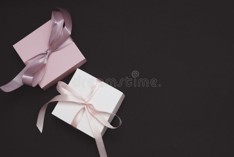 有一把桃红色和白色丝带弓的白色和桃红色礼物盒在布朗背景 平的位置,顶视图,拷贝空间 定调子 库存图片