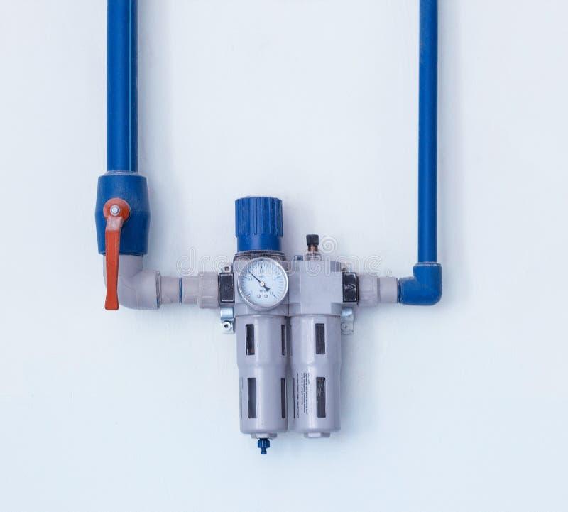 有一把水位标尺的现代过滤器清洗的从残骸和重金属,位于墙壁,水管水净化 库存照片