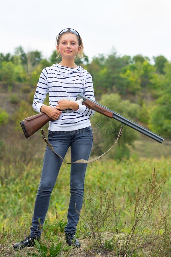 有一把猎枪的女孩在室外 库存照片