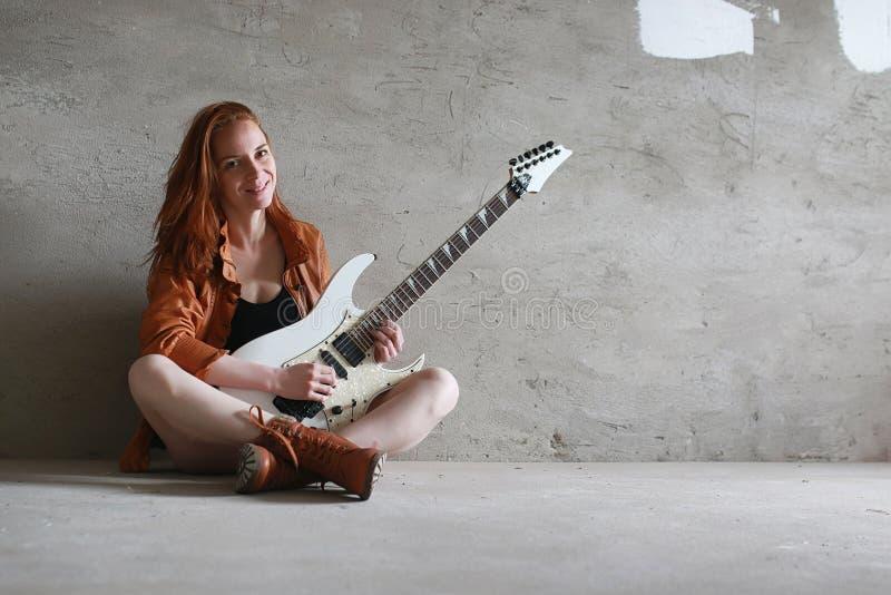 有一把电吉他的年轻红发女孩 岩石音乐家gir 免版税库存图片