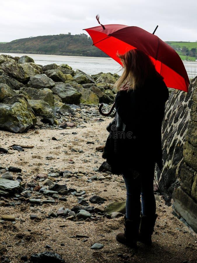 有一把红色伞的少妇 免版税图库摄影