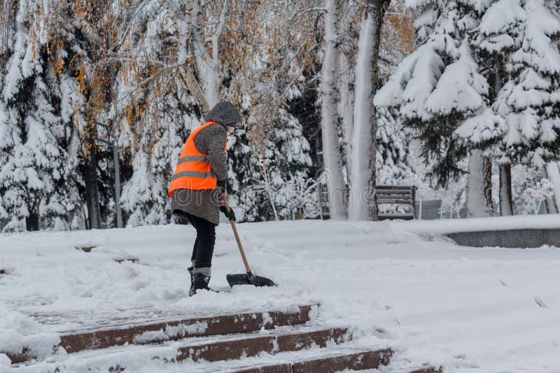 有一把铁锹的妇女在橙色背心清洗雪 库存照片