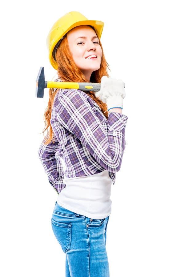 有一把锤子的成功的妇女在一顶黄色安全帽反对 免版税库存图片