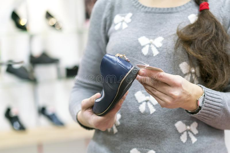 有一把长的大镰刀的一个女孩选择在鞋店的鞋子 免版税库存图片