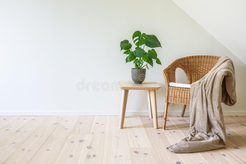 有一揽子和一张木桌的藤条扶手椅子 免版税库存照片