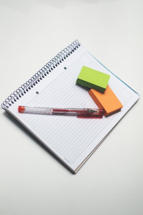 有一支红色笔的没记录的笔记本和关于它的五颜六色的笔记 库存图片