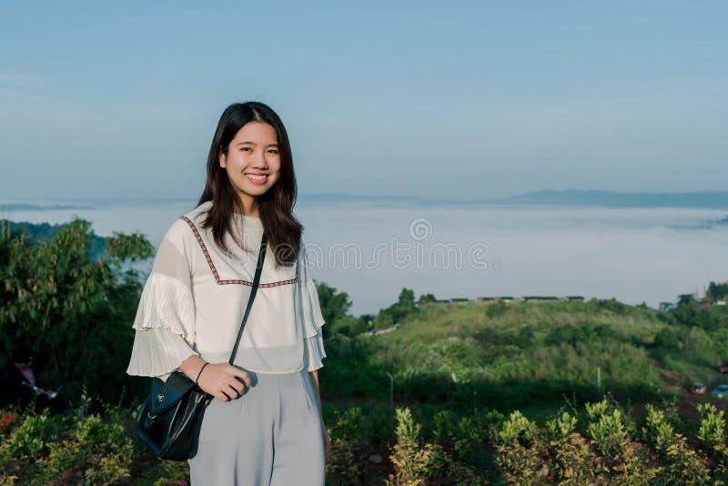 有一明亮的白色衬衫的一名可爱的亚裔妇女 站立在雾和山后的旅游区与微笑  免版税库存照片