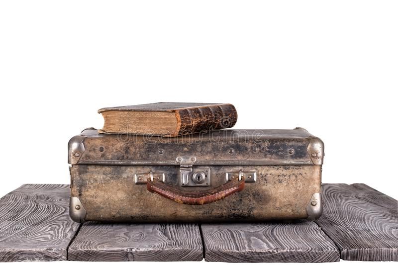 有一本书的一个老手提箱在木板 免版税库存图片